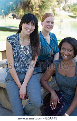 Businesswomen smiling together in park - Stock Photo