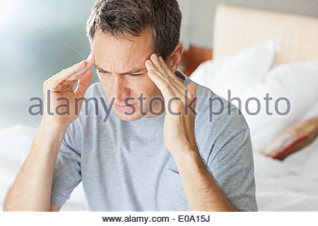 Man with headache rubbing forehead - Stock Photo