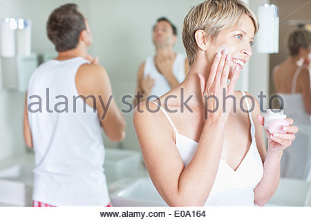 Woman applying face cream in the morning - Stock Photo