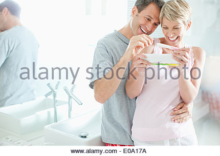 Excited couple looking at pregnancy test - Stock Photo