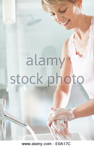 Woman washing hands in the bathroom - Stock Photo