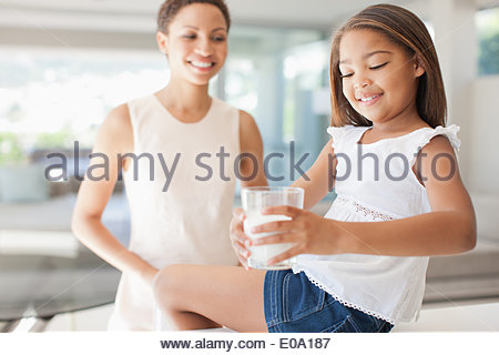 Mother watching daughter drink glass of milk - Stock Photo