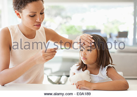 Mother taking daughterÂ's temperature - Stock Photo