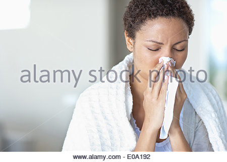Sick woman blowing her nose - Stock Photo