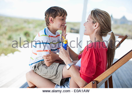 Mother putting sunscreen on boy - Stock Photo