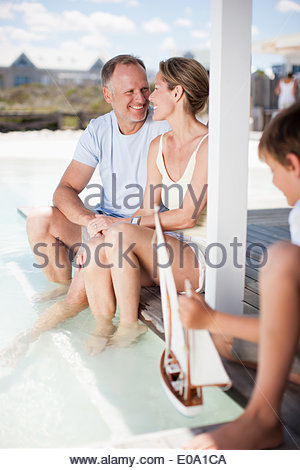 Boy playing with miniature boat in pool - Stock Photo