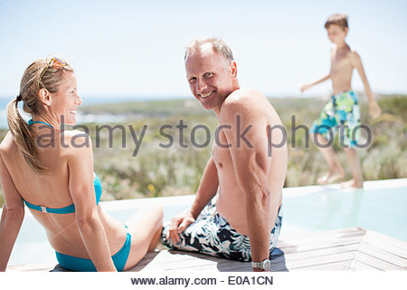 Family sitting by swimming pool - Stock Photo