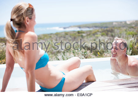 Couple swimming in pool - Stock Photo
