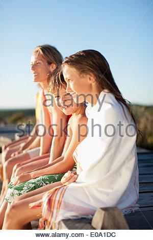 Family sitting on pier near beach - Stock Photo