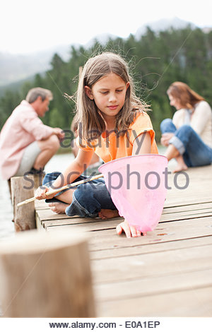Girl with net sitting on pier by lake - Stock Photo