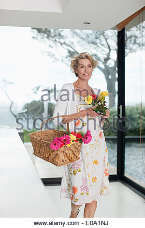 Mature woman with basket of flowers - Stock Photo