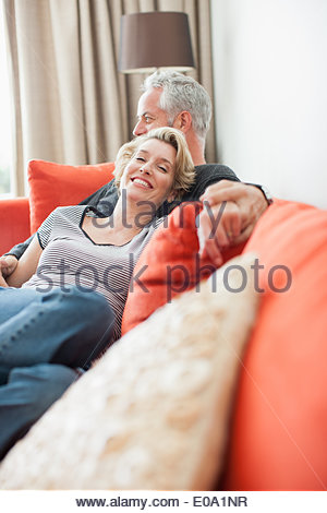 Mature couple laying on sofa holding hands - Stock Photo