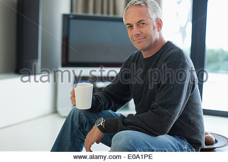 Man drinking coffee in living room - Stock Photo