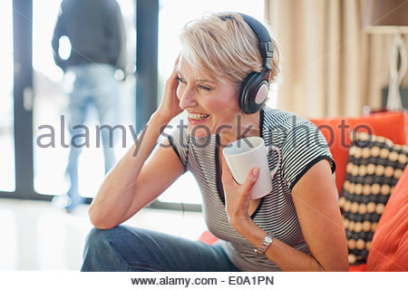 Woman drinking coffee and listening to headphones - Stock Photo