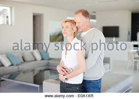 Couple cuddling in living room - Stock Photo