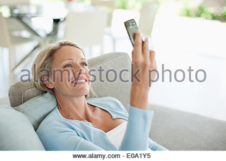 Woman laying on sofa text messaging on cell phone - Stock Photo