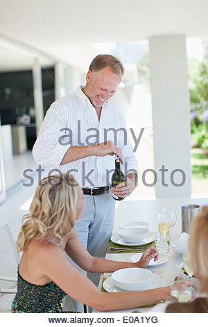 Man opening wine bottle for wife - Stock Photo