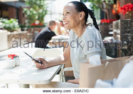 Woman using cell phone at cafe - Stock Photo
