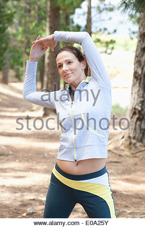 Woman stretching before run in forest - Stock Photo