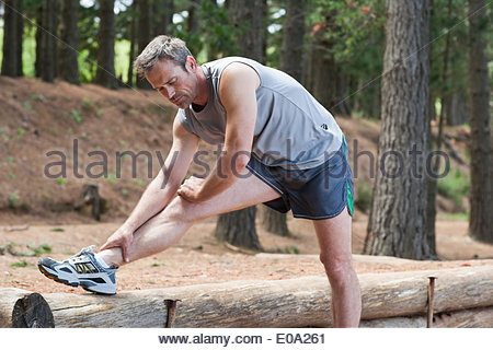 Man stretching before run in forest - Stock Photo