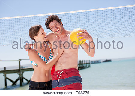 Friends playing volleyball on beach - Stock Photo