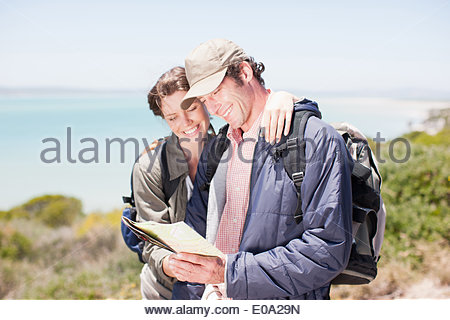 Couple hiking in remote area and looking at map - Stock Photo
