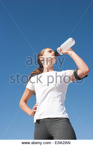 Woman runner drinking from water bottle - Stock Photo