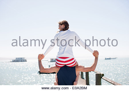 Man carrying wife on shoulders on pier at ocean - Stock Photo