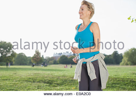 Smiling woman jogging in park - Stock Photo