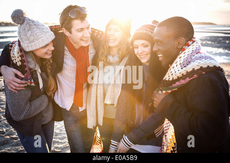 Five adult friends wrapped in a blanket on the beach - Stock Photo