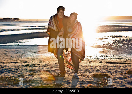 Couple wrapped in a blanket walking on the beach - Stock Photo