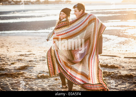 Couple wrapped in a blanket strolling on the beach - Stock Photo