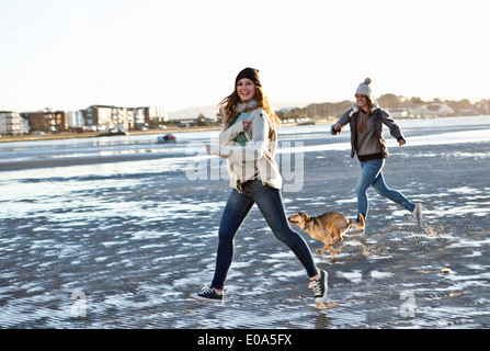 Two female friends running with dog on the beach - Stock Photo