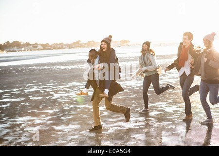 Five adult friends running on the beach - Stock Photo