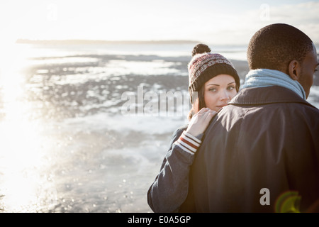 Romantic young couple walking on the beach - Stock Photo