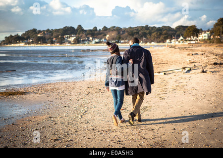Romantic young couple strolling on the beach - Stock Photo