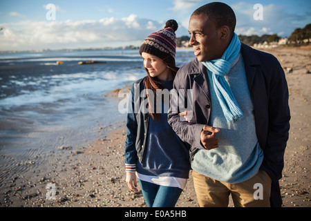 Romantic young couple arm in arm on the beach - Stock Photo