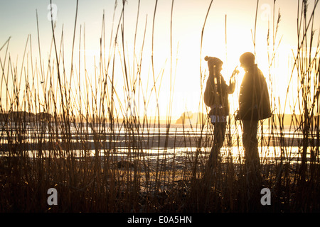 Silhouette of romantic young couple on the beach - Stock Photo