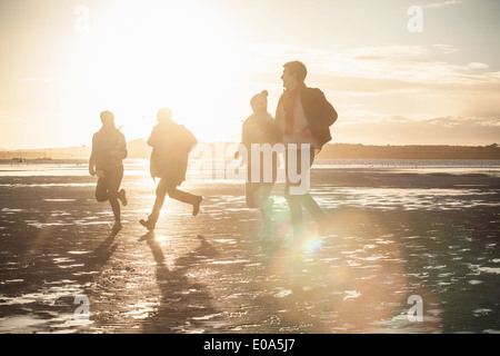 Adult friends racing each other on the beach - Stock Photo