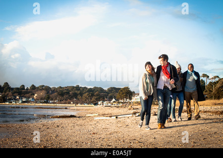 Five adult friends out walking on the beach - Stock Photo