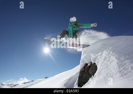 Young woman jumping with snowboard, Mayrhofen, Tyrol, Austria - Stock Photo