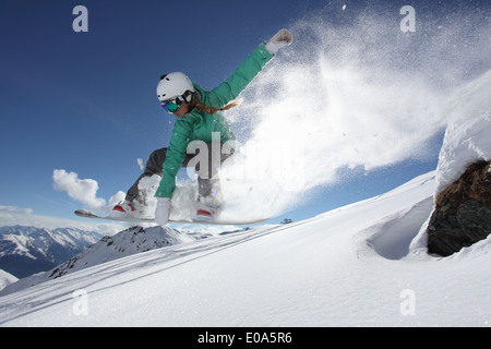 Young woman jumping on snowboard, Mayrhofen, Tyrol, Austria - Stock Photo