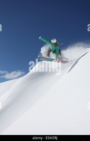 Young woman snowboarding on steep slope, Mayrhofen, Tyrol, Austria - Stock Photo