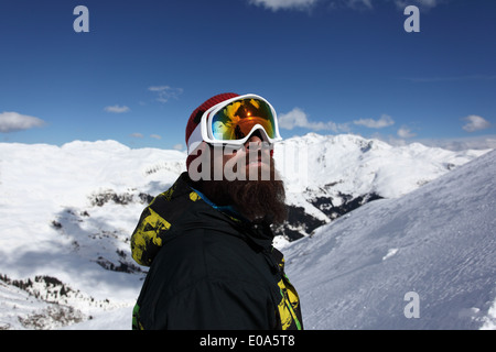 Mid adult man skier looking up at mountain, Mayrhofen, Tyrol, Austria - Stock Photo