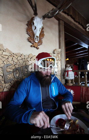 Mid adult male skier enjoying restaurant meal, Tyrol, Austria - Stock Photo