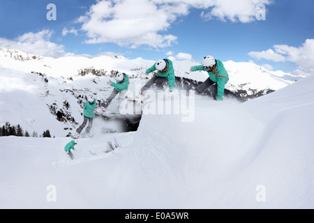Multi exposure of young woman snowboarding on mountain, Mayrhofen, Tyrol, Austria - Stock Photo