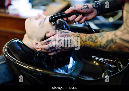 Close up of barber washing young mans hair - Stock Photo