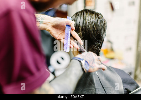 Close up of barber cutting young mans hair - Stock Photo
