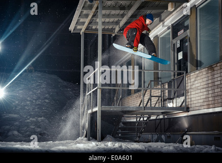 Mid adult male snowboarder jumping mid air from building at night - Stock Photo