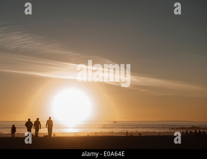 Silhouetted people strolling on beach at sunset, Venice Beach, California, USA - Stock Photo